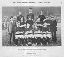 Photographie en noir et blanc d'une équipe de football faisant la queue avant un match. Quatre joueurs, vêtus d'une chemise sombre, d'un short léger et de chaussettes noires, sont assis. Quatre autres joueurs se tiennent immédiatement derrière eux, et trois autres se trouvent à un niveau supérieur dans la rangée arrière. Deux hommes en costume se tiennent de chaque côté des joueurs.