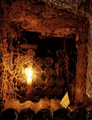 Old bottles of wine aging by candle light