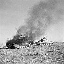 Crusader tank Britania melewati Panzer IV Jerman yang terbakar di tengah gurun