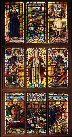 A vertical rectangular stained glass window with nine panels, each holding one or more human figures