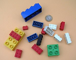 LEGO and DUPLO bricks with a 1 EURO coin for scale