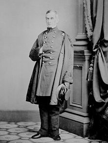 Full length photograph of a Civil War-era United States army officer. He is posed in a studio in front of a decorative column with one hand inside his coat.