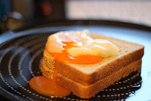 English: A single broken poached egg on 2 piec...