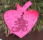 """Heart-shaped sign reading """"We stand with Comet"""""""