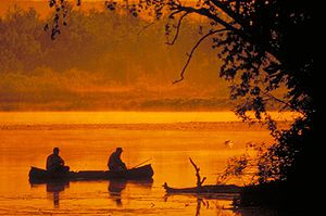 Fisherman in a canoe at sunset