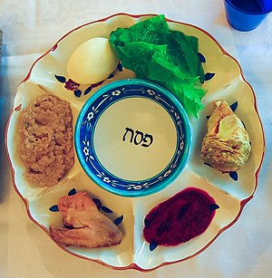 Passover plate with symbolic foods: maror, egg...