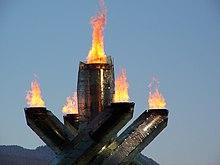 Quatre piliers avec la flamme à leurs sommets entourant un cinquième piller, seul, au milieu, avec aussi la flamme au sommet. Le fond est le ciel avec la montagne.
