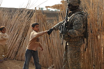 English: An Iraqi boy gives a fist bump to U.S...