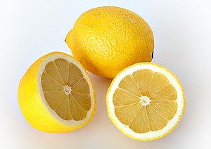 This image shows a whole and a cut lemon.