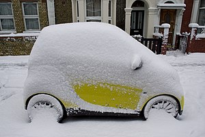Snow on a yellow SMART car in London.