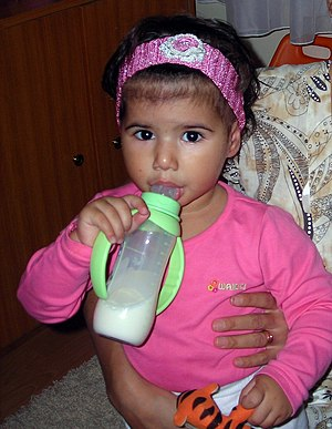 English: Girl with a feeding bottle
