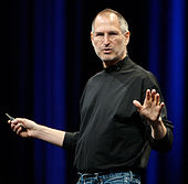 Waist-high portrait of man in his fifties wearing a black turtle-neck shirt and blue jeans, gesturing in front of a blue curtain