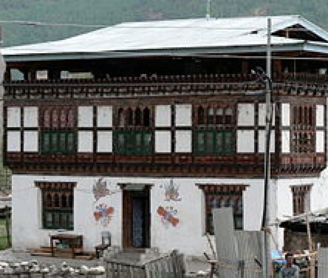A Bhutanese House In Paro With Multi Colored Wood Frontages Small Arched Windows And A Sloping Roof