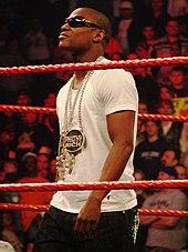 Mayweather, portant des lunettes de soleil, un t-shirt blanc et des chaînes, dans un ring de lutte avec des cordes rouges