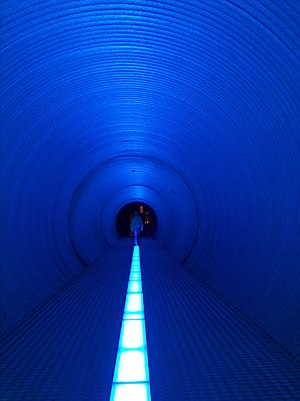 A person in a long tunnel at a science museum