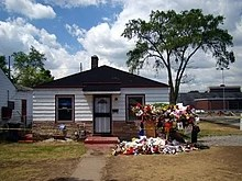 The single-story house has white walls, two windows, a central white door with a black door frame, and a black roof. In front of the house there is a walkway and multiple colored flowers and memorabilia.