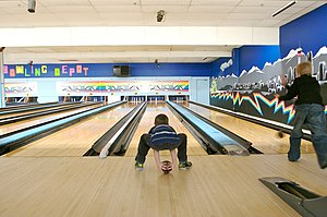 A young boy five-pin bowling in Canada