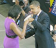 """De Obama's Tegenover Elkaar en bump vuisten op Het Podium.  Ze Draagt Een paarse jurk en HIJ Een donker pak Draagt.  Verschillende borden lezen """"CHANGE WIJ Kunnen Geloven"""" en Nemen Diverse fotografen foto's."""