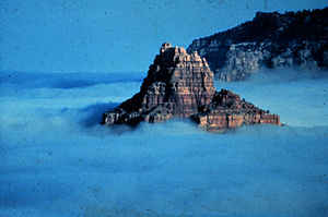A rocky peak rises from a sea of fog in an Ari...