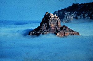 A rocky peak rises from a sea of fog in an Ari...
