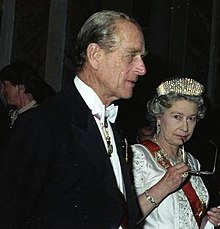 Behind her husband, Elizabeth holds a pair of spectacles to her mouth in a thoughtful pose