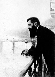 A long-bearded man in his early forties leaning over a railing with a bridge in the background. Dressed in a black overcoat, he gazes blankly into the distance with his hands clasped.