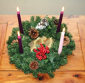 Advent wreath with one rose candle and three p...