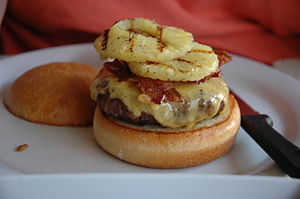 Cheeseburger topped with bacon and grilled pin...