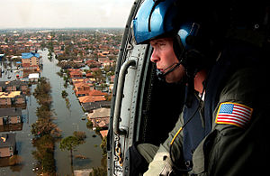 A U.S. Coast Guardsman searches for survivors ...