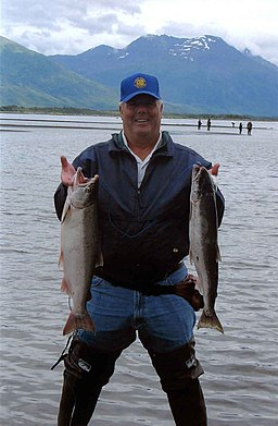 Fisherman holds fish silver coho salmon