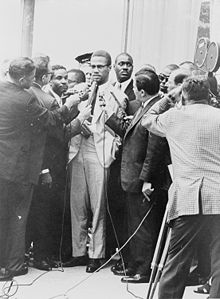 A 39-year-old man is surrounded by reporters with microphones, while a television camera captures the scene