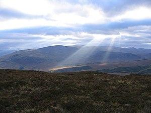 English: Sun beams lighting up the glens Stron...