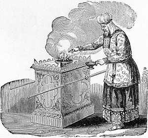 High priest offering incense on the altar, as ...