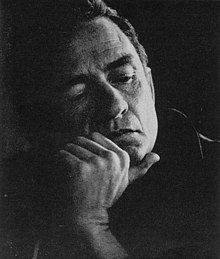 A black-and-white photo of Cash holding his face