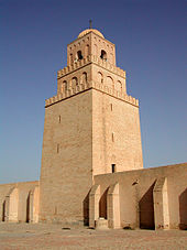 A square stone tower rises high above a wall.