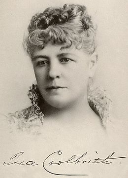 """A fine charcoal portrait of Ina Coolbrith in her 30s or 40s, shown from the neck up, wearing a garment with a high, open collar made of lace, with hair curled and secured atop the head, looking slightly to the left. A fountain pen signature is below the portrait, reading """"Ina Coolbrith"""", the letter """"c"""" writ large to sweep underneath the next five letters."""