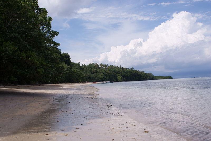 Een door massatoerisme overspoeld strand op Bunaken