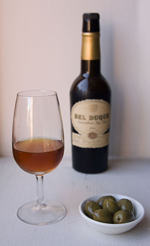 A glass of amontillado sherry, with olives