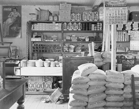 """Packaged and loose goods are stacked on shelves and the floor. Items visible on the walls include a calendar showing """"July 1936"""" and a Coca-Cola advertisement. Visible items for sale include loose dishes, lanterns, dustpans, padlocks, rope, Mason jars, boxed soaps, boxes of shot-gun shells, canned goods, bags of self-rising flour. Rolls of butcher-paper visible at left. A safe is at centre, partially behind bags of flour."""
