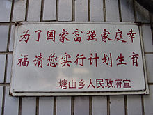 A white sign with two lines of red Chinese characters and a smaller one beneath them on a background of white tile