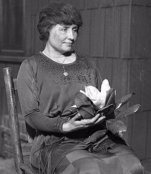 Helen Keller sitting holding a magnolia flower...