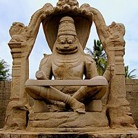 Brown stone statue of smiling deity sitting cross-legged under arch