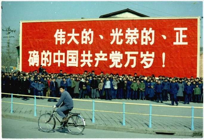 Spectators in front of a large sign on Nixon's motorcade route in China. - NARA - 194413