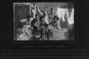 6 smiling women under tenement clothesline; ca...