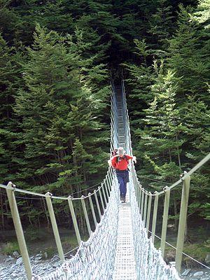 A tramper crossing a swing bridge on the Huxle...