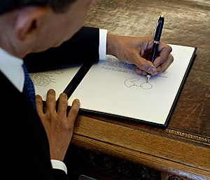 English: President Barack Obama writes at his ...