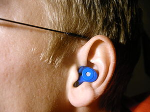 Individual silicone earplug worn at ear with E...