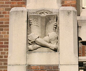 English: Concrete relief of a boy reading a bo...