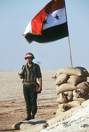 A member of a Syrian honor guard stands beside...