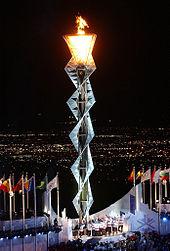 Une armature en acier entrelacé avec une flamme allumée au sommet.